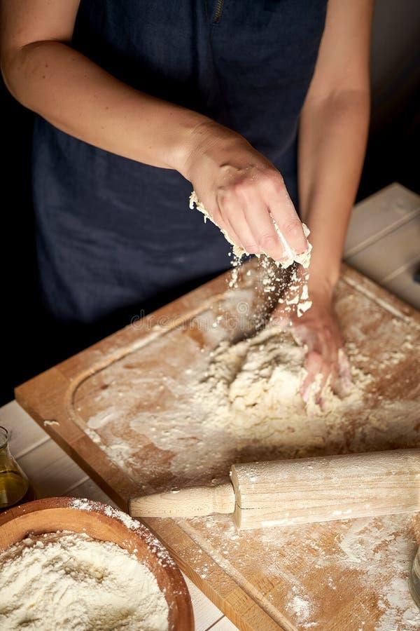 La mujer prepara la pasta en tablero de los pasteles con la harina y el rodillo en la tabla de madera foto de archivo libre de regalías