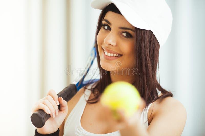 La mujer presenta con una estafa de tenis mientras que sostiene la pelota de tenis imagenes de archivo
