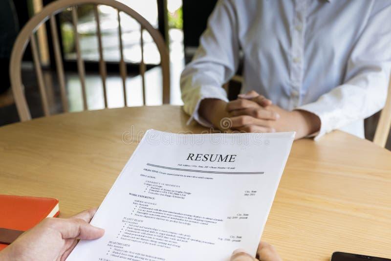 La mujer presenta la solicitud de trabajo, entrevistador que lee un curriculum vitae foto de archivo libre de regalías