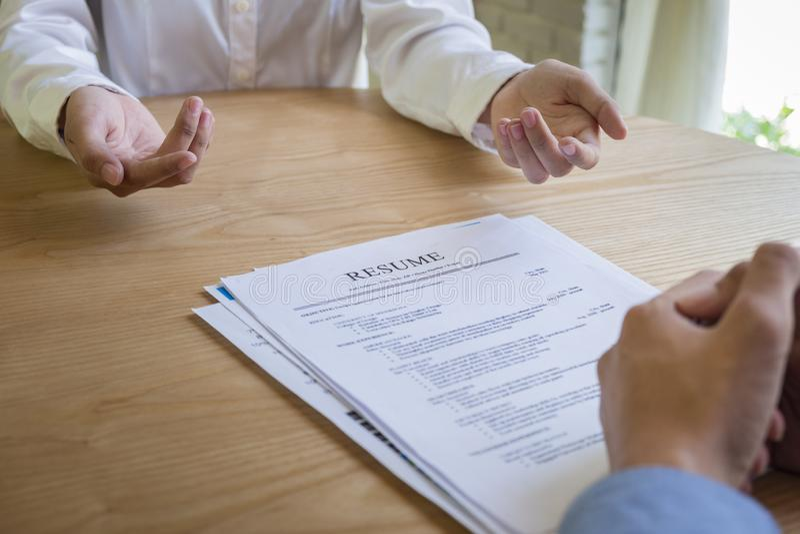 La mujer presenta la solicitud de trabajo, entrevistador que lee un curriculum vitae fotografía de archivo libre de regalías