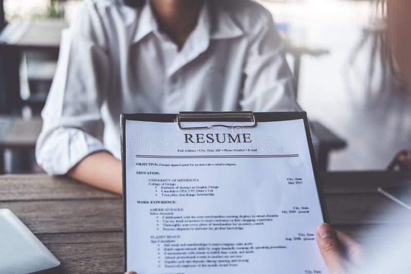 La mujer presenta la solicitud de trabajo, entrevistador que lee un curriculum vitae fotografía de archivo