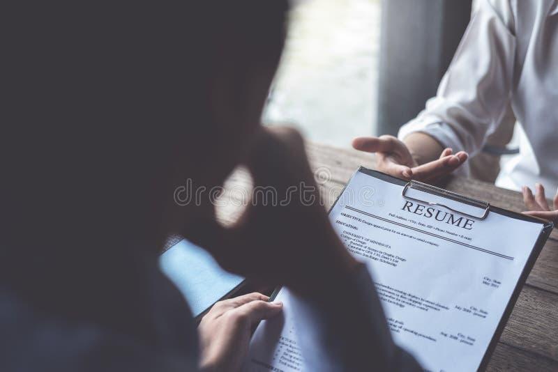 La mujer presenta la solicitud de trabajo, entrevistador que lee un curriculum vitae fotos de archivo