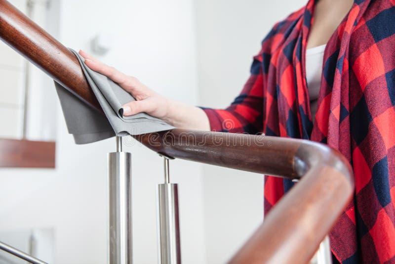 La mujer pule la barandilla de madera de las escaleras imagen de archivo