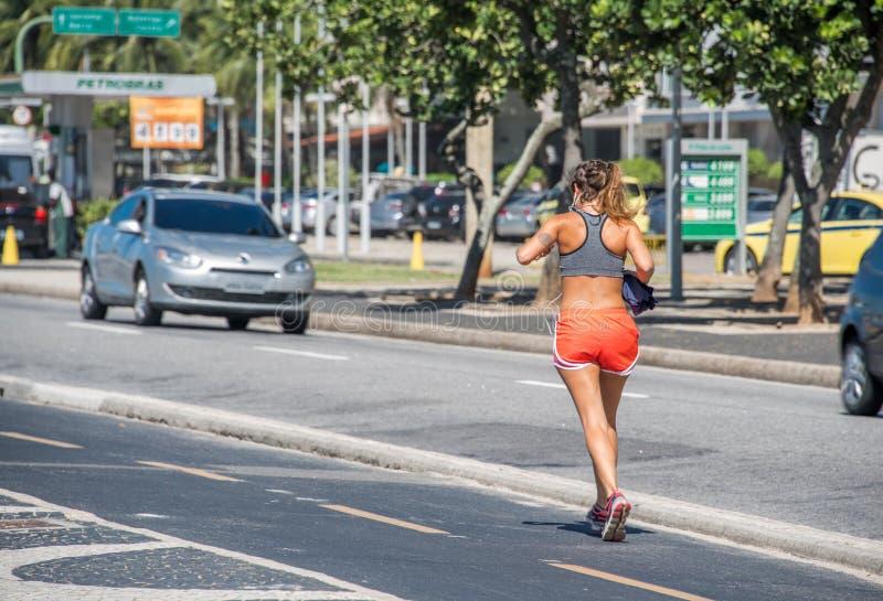 La mujer que activa en la trayectoria corriente frente al mar delante del camino del tráfico en la playa de Copacabana fotografía de archivo