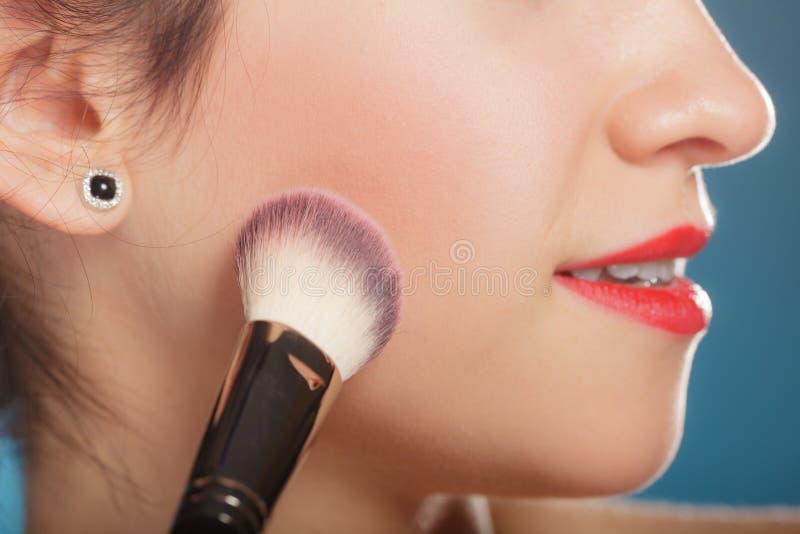 La mujer que aplica el colorete se ruboriza maquillaje fotografía de archivo libre de regalías
