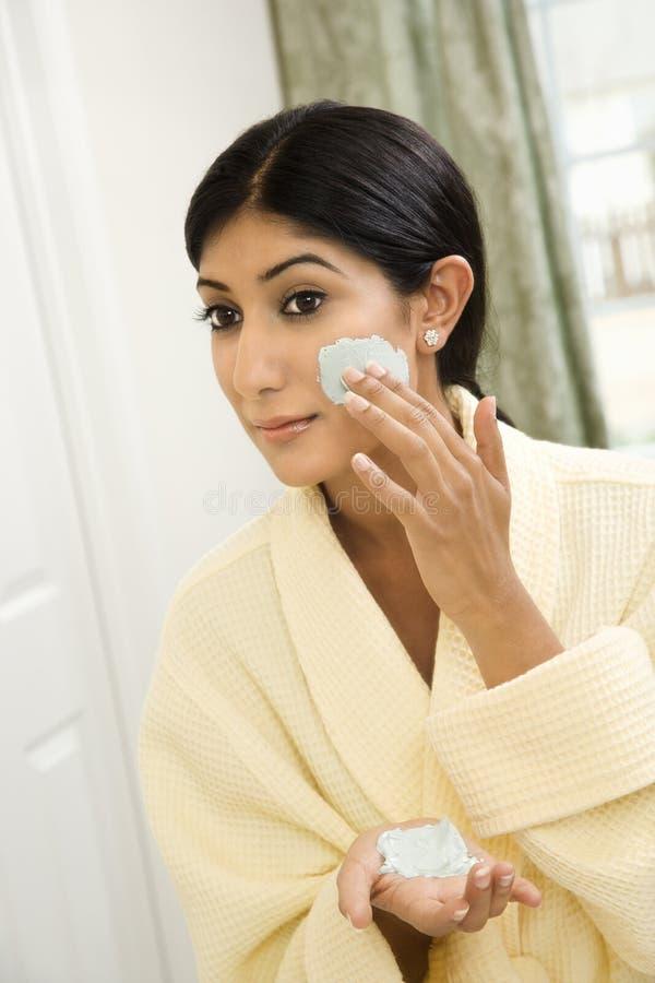 La mujer que aplica el facial friega. imagen de archivo libre de regalías