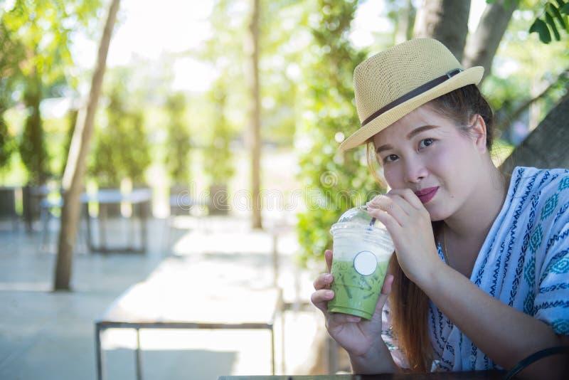 La mujer que bebía el té verde helado, mirando la cámara, empañó el backgr imagen de archivo