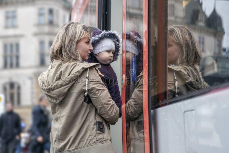 La mujer que detiene a un niño entra en la puerta del transporte público foto de archivo