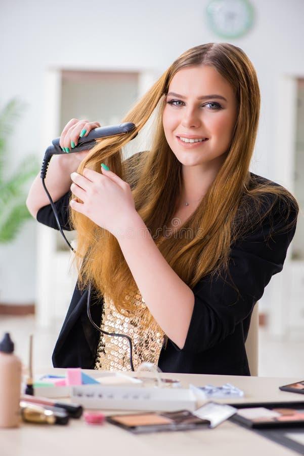 La mujer que diseña su pelo con el hairdryer fotografía de archivo libre de regalías