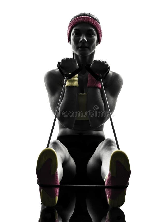 La mujer que ejercita resistencia del entrenamiento de la aptitud congriega la silueta foto de archivo