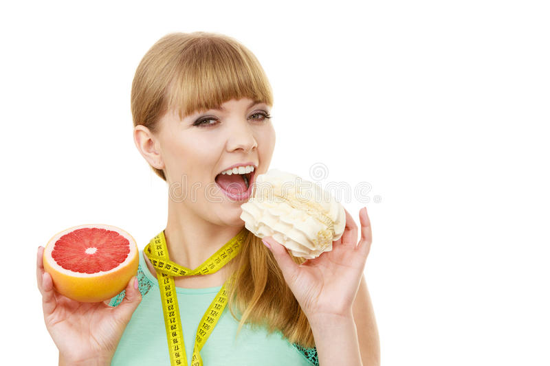 La mujer que elige la fruta o la torta toma la decisión dietética fotografía de archivo