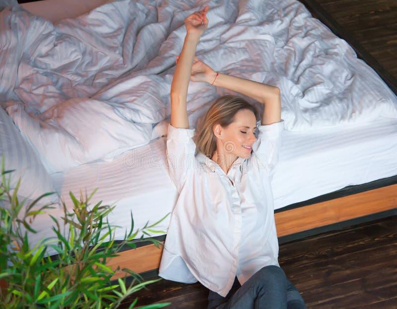 La mujer que estira en cama después de despierta imagen de archivo