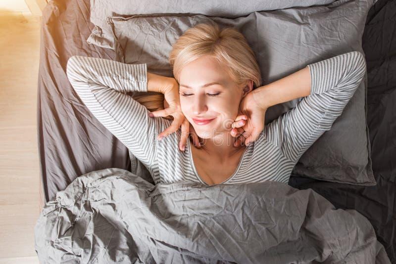 La mujer que estira en cama despu?s de despierta foto de archivo libre de regalías