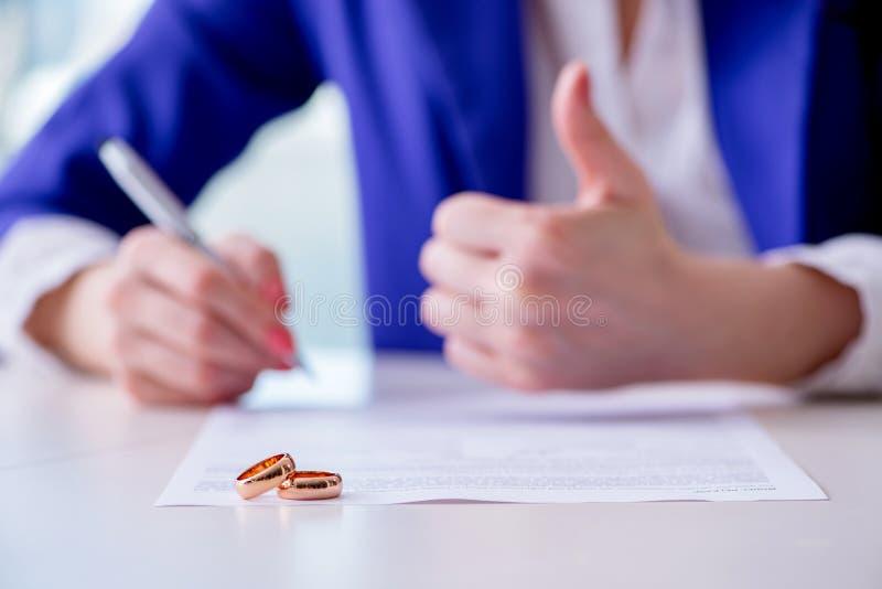 La mujer que firma el acuerdo prenuptial ante el tribunal foto de archivo