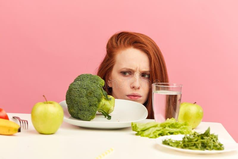 La mujer que frunce el ce?o tiene aversi?n verduras en la tabla con la mueca de disgusto aislada fotos de archivo
