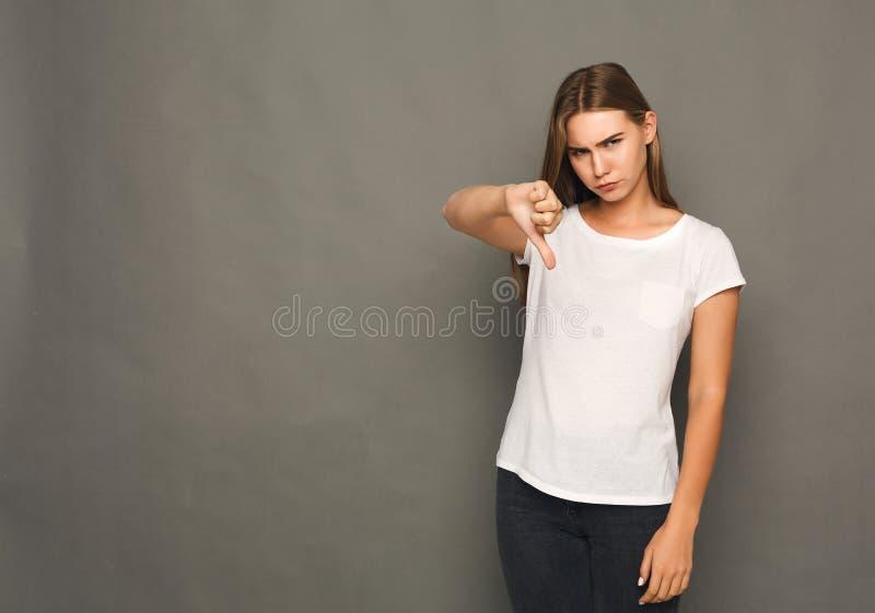 La mujer que gesticula el pulgar abajo firma imagenes de archivo