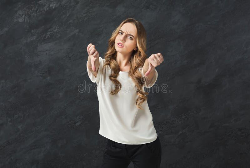 La mujer que gesticula los pulgares abajo firma foto de archivo