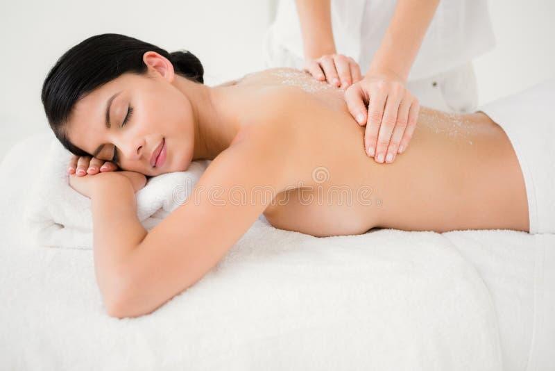 La mujer que goza de una sal friega masaje fotos de archivo