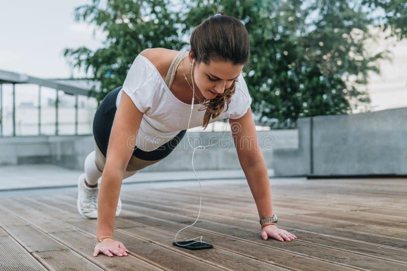 La mujer que hace deportes ejercita al aire libre La muchacha hace el tablón mientras que mira la pantalla del smartphone, escuch imagen de archivo libre de regalías