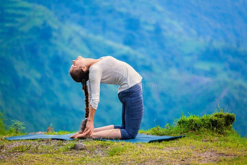 La mujer que hace el camello de Ustrasana del asana de la yoga presenta al aire libre imagen de archivo
