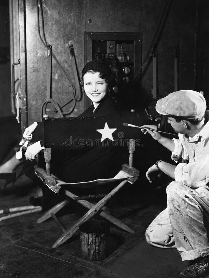 La mujer que hace el nombre pintar encendido apoya de silla de los directores (todas las personas representadas no son vivas más  fotos de archivo