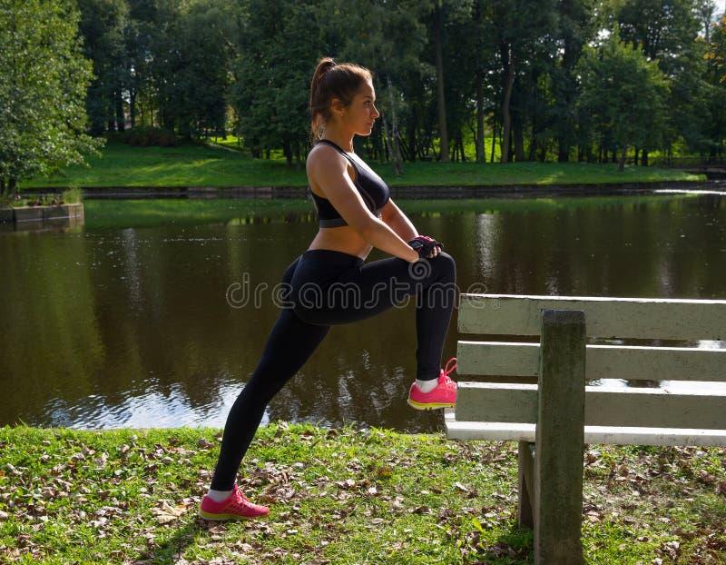 La mujer que hace estirar ejercita en parque antes de entrenar foto de archivo libre de regalías