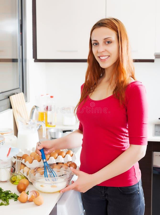 La mujer que hace los huevos revueltos con bate fotos de archivo libres de regalías