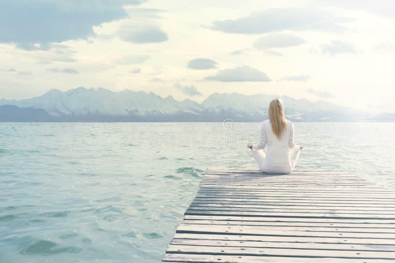 La mujer que hace yoga ejercita delante de un paisaje espectacular imagen de archivo libre de regalías