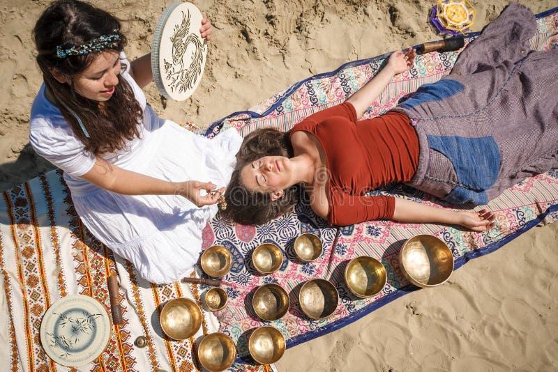La mujer que juega un canto rueda también conocido como cuencos del canto del tibetano, cuencos Himalayan Fabricación de masaje s fotos de archivo libres de regalías