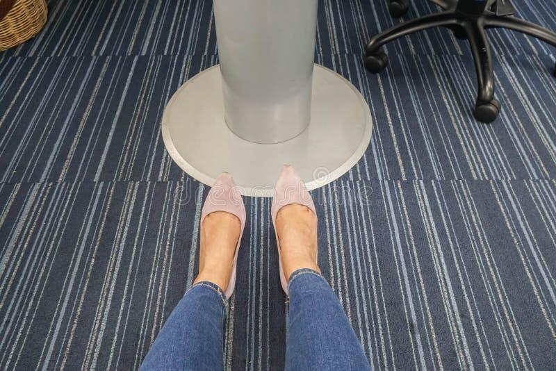 La mujer que las piernas llevan los tejanos con el tacón alto púrpura se sienta en sala de reunión fotos de archivo libres de regalías
