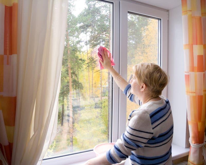 La mujer que lava una ventana. fotografía de archivo