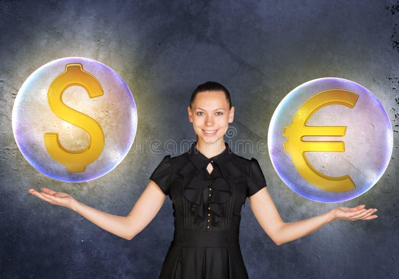 La mujer que lleva a cabo el dólar y el euro firma adentro burbujea imagen de archivo libre de regalías