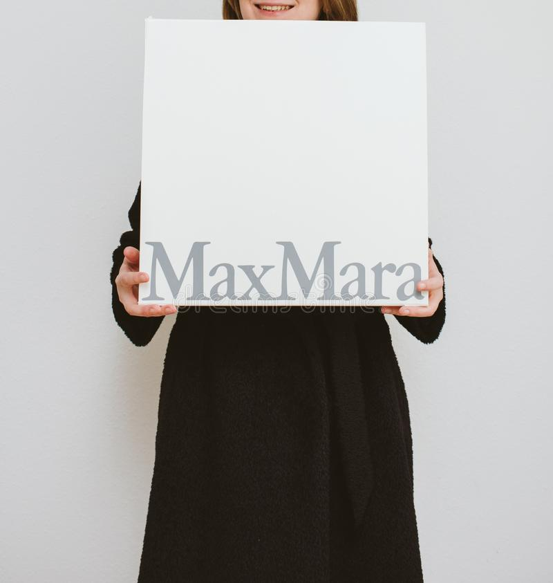 La mujer que lleva a cabo la moda de Max Mara viste la caja de cartón de lujo foto de archivo libre de regalías