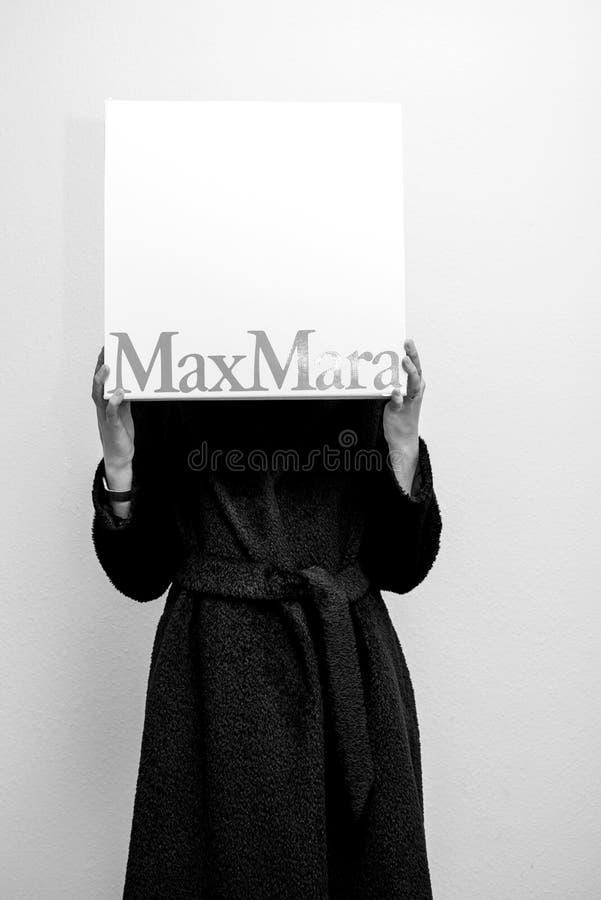 La mujer que lleva a cabo la moda de Max Mara viste la caja de cartón de lujo imagen de archivo