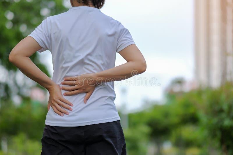 la mujer que lleva a cabo su lesión de los deportes, muscle doloroso durante el entrenamiento imagen de archivo
