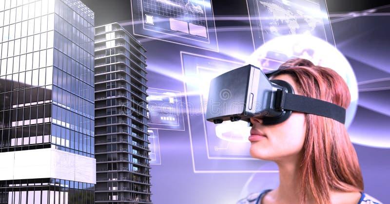 La mujer que lleva las auriculares de la realidad virtual con los edificios altos con el mundo y las pantallas interconectan foto de archivo libre de regalías