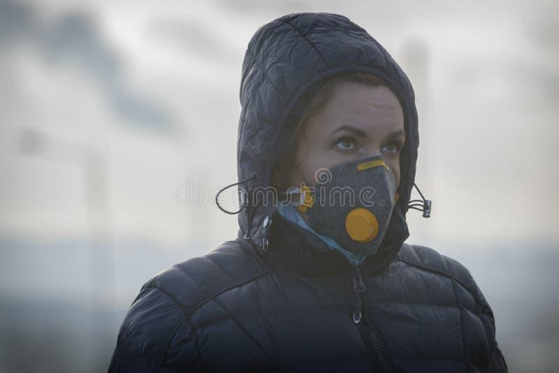 La mujer que lleva un anticontaminación real, contra la niebla y los virus la mascarilla imágenes de archivo libres de regalías