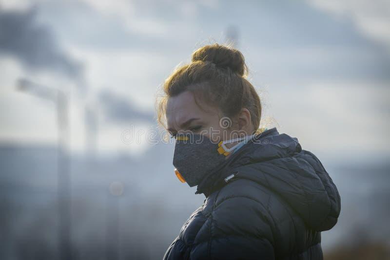 La mujer que lleva un anticontaminación real, contra la niebla y los virus la mascarilla foto de archivo