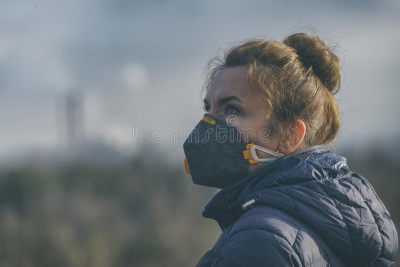 La mujer que lleva un anticontaminación real, contra la niebla y los virus la mascarilla foto de archivo libre de regalías