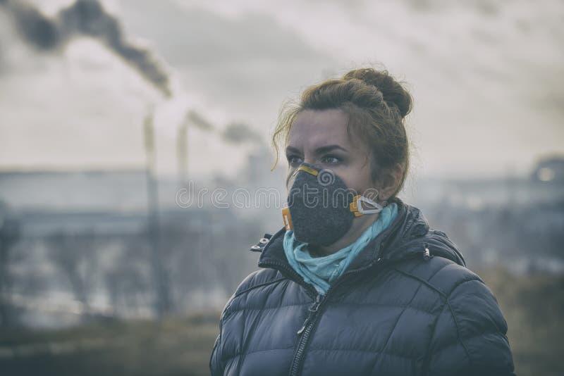 La mujer que lleva un anticontaminación real, contra la niebla y los virus la mascarilla fotografía de archivo