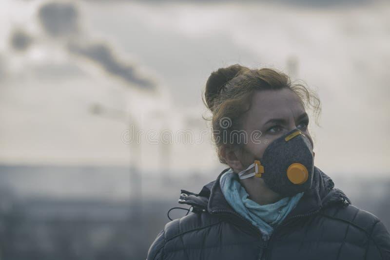 La mujer que lleva un anticontaminación real, contra la niebla y los virus la mascarilla fotografía de archivo libre de regalías