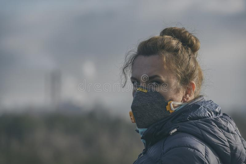 La mujer que lleva un anticontaminación real, contra la niebla y los virus la mascarilla imagen de archivo