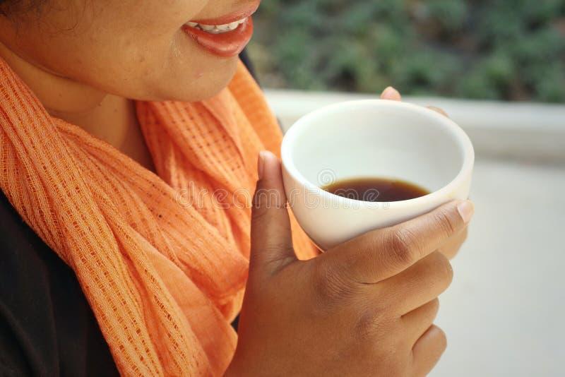La mujer que lleva una camisa negra está bebiendo el café fotos de archivo