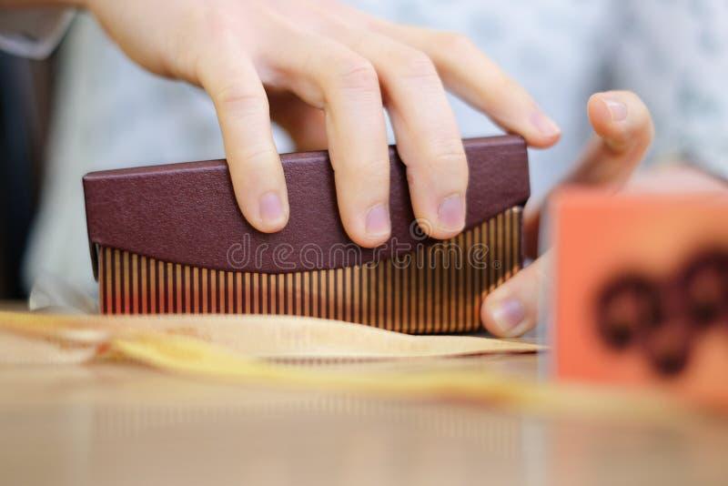 La mujer que la mano del ` s abre la caja de regalo allí puede ser algo dentro imágenes de archivo libres de regalías