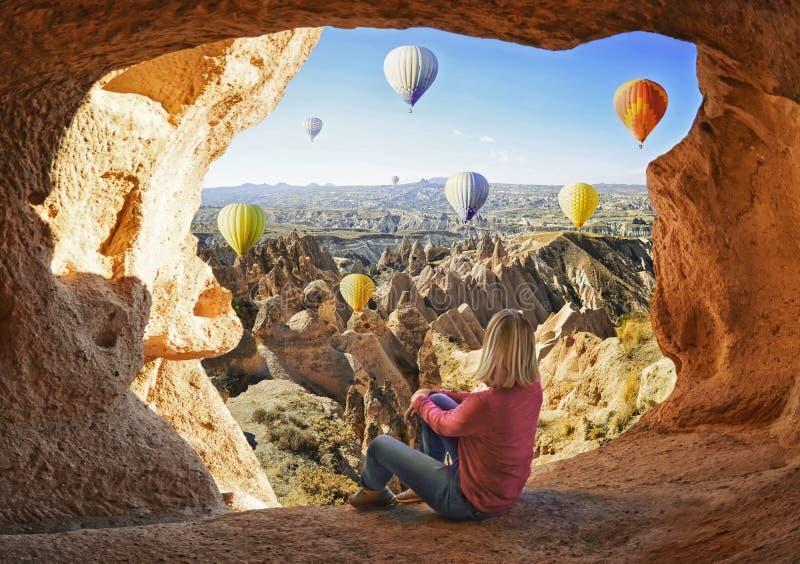 La mujer que mira como el aire caliente colorido hincha volar sobre el valle en Cappadocia fotografía de archivo