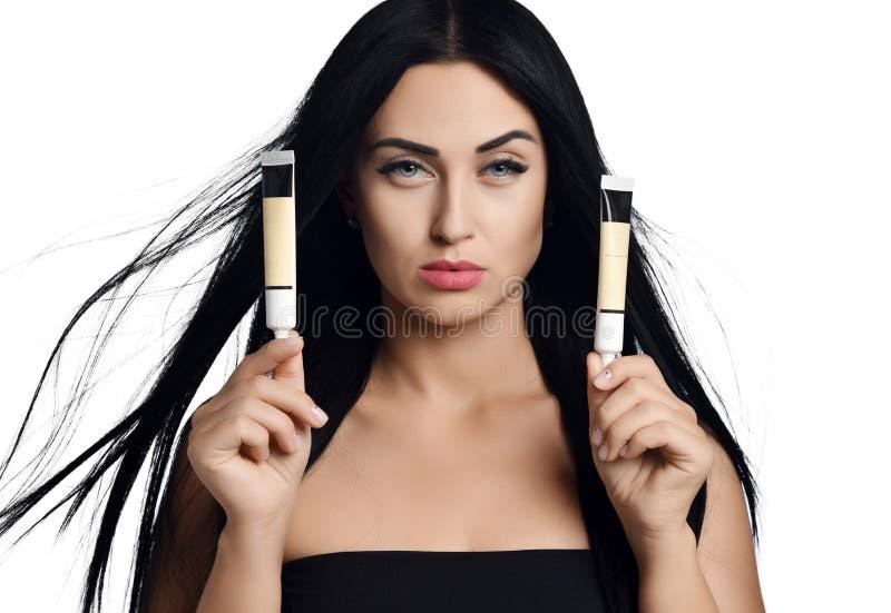 La mujer que la morenita con el pelo que agita en el viento compara dos cosméticos bate en pequeños tubos en blanco Concepto del  imagen de archivo libre de regalías