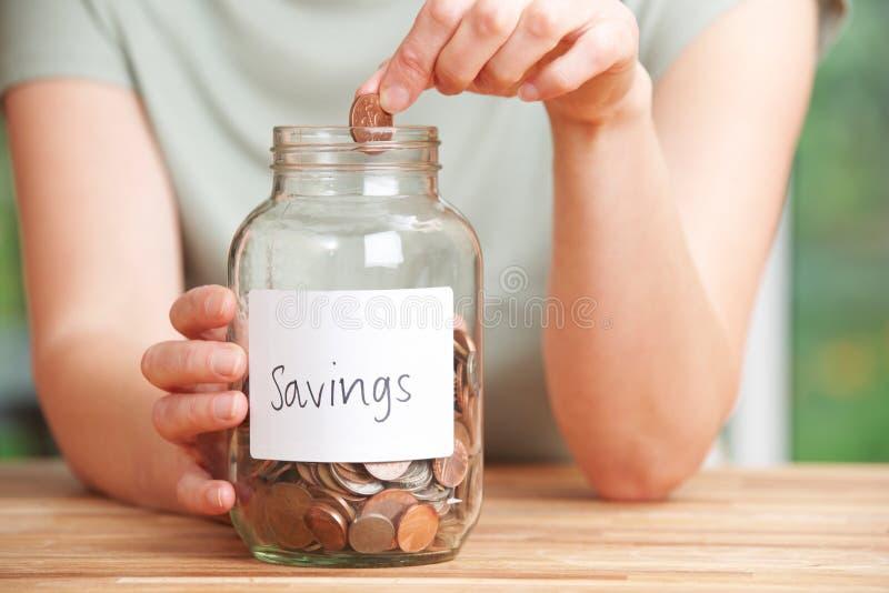 La mujer que ponía la moneda en el tarro etiquetó ahorros foto de archivo