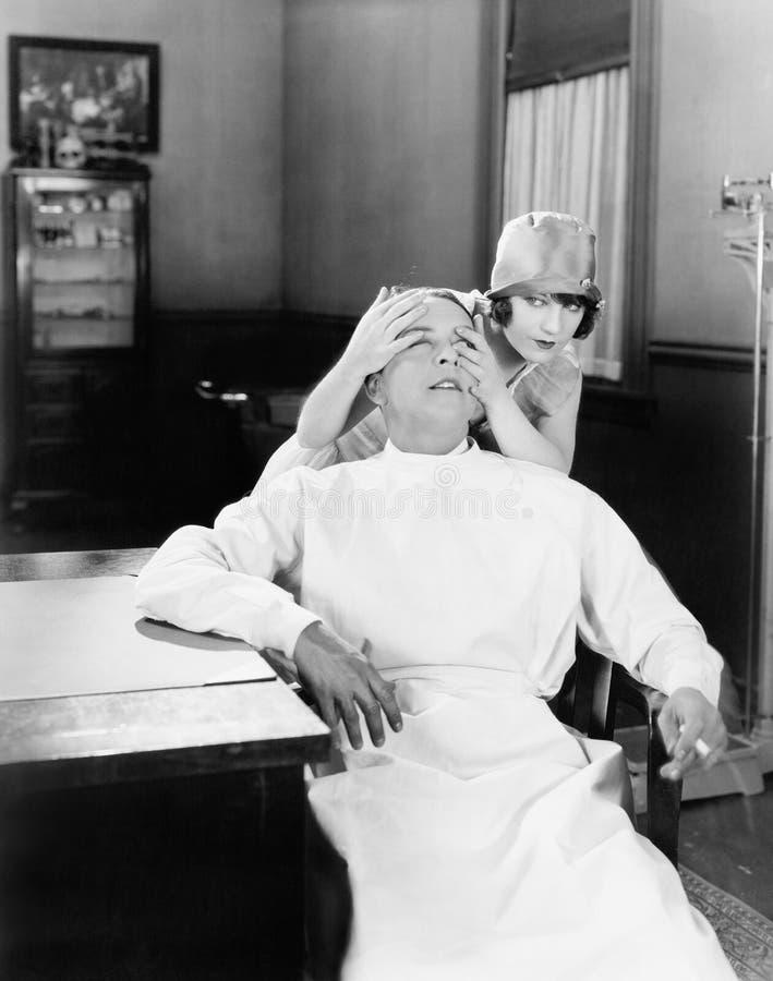 La mujer que pone sus manos sobre los doctores observa juguetónamente (todas las personas representadas no son vivas más largo y  fotografía de archivo libre de regalías