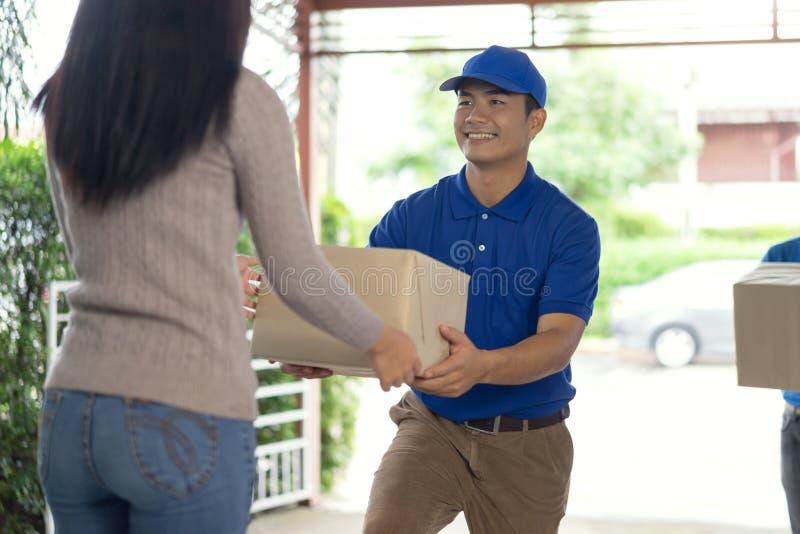 La mujer que recibe el paquete del hombre de entrega, hombre de entrega trae la entrega de la caja del paquete Servicio rápido y  fotografía de archivo