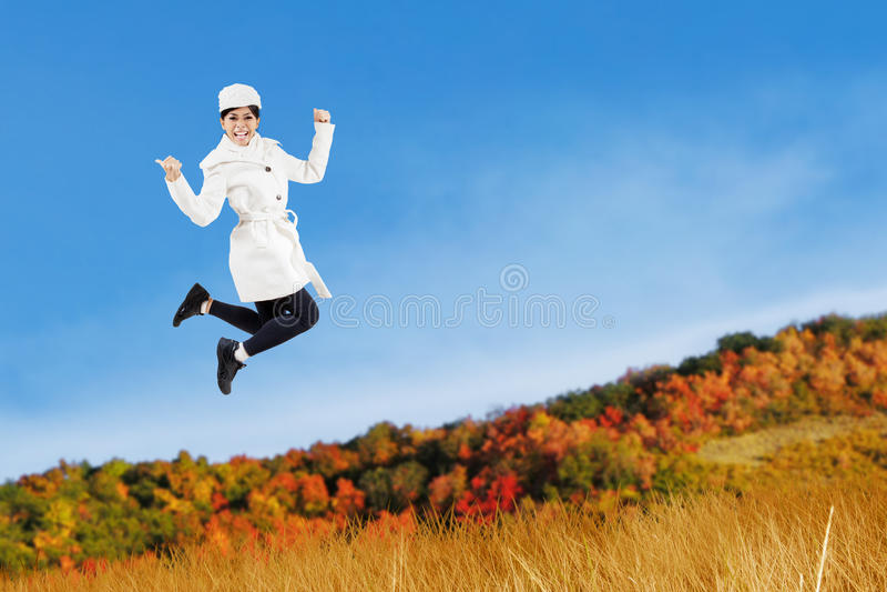La mujer que salta con una chaqueta del otoño imagen de archivo